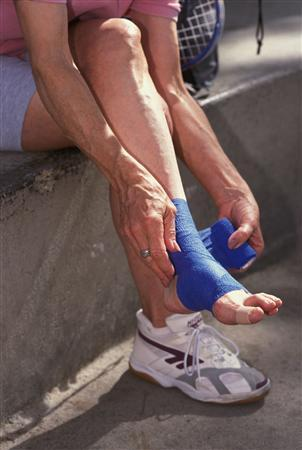 Elderly woman wrapping her sprained ankle after an injury playing raquetball at a gym in Los Angeles, California.